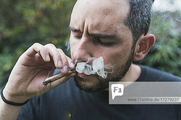 Handsome man smoking marijuana joint outdoors