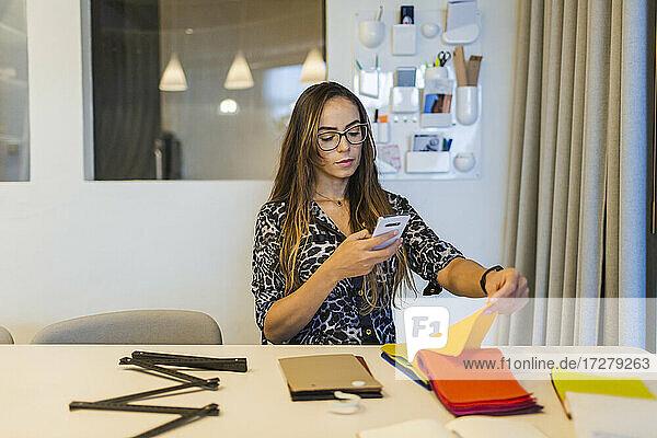 Kreative Geschäftsfrau  die ein Stoffmuster mit ihrem Smartphone fotografiert  während sie am Schreibtisch im Büro sitzt