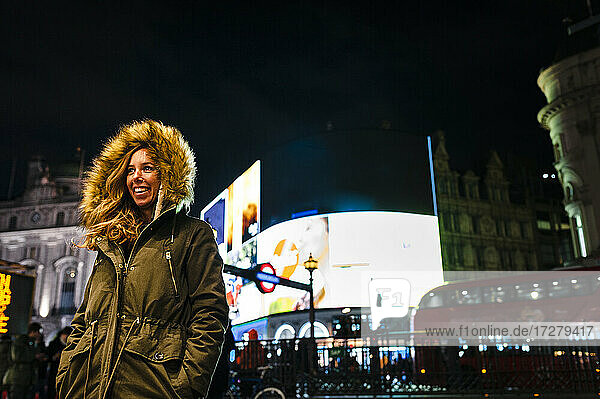 Woman in warm clothing standing at Regent Street during Christmas in city at London  UK