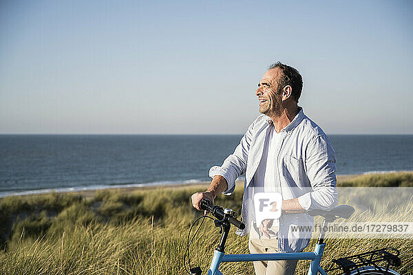 Cheerful mature man looking away while standing with bicycle at beach against clear sky