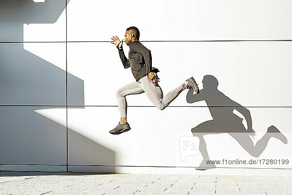 Young athlete running against white wall