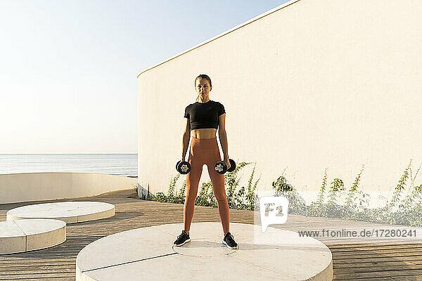 Sportswoman lifting dumbbells while exercising on pedestal during sunrise