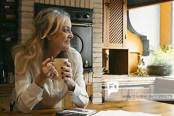 Lächelnde Frau  die Kaffee trinkt und sich zu Hause auf die Kücheninsel stützt