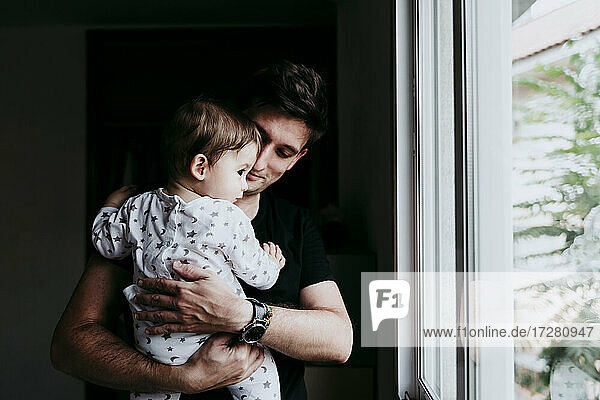 Father holding son while looking through window at home