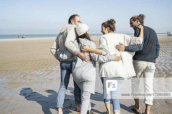 Family with arms around each other walking at beach