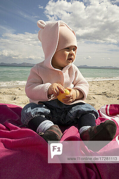 Baby girl sitting on sand at beach during sunny day