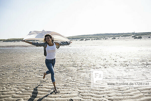 Carefree woman running while holding blanket at beach on sunny day