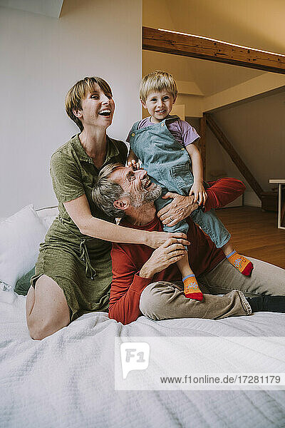 Mother and father embracing son while sitting on bed at home
