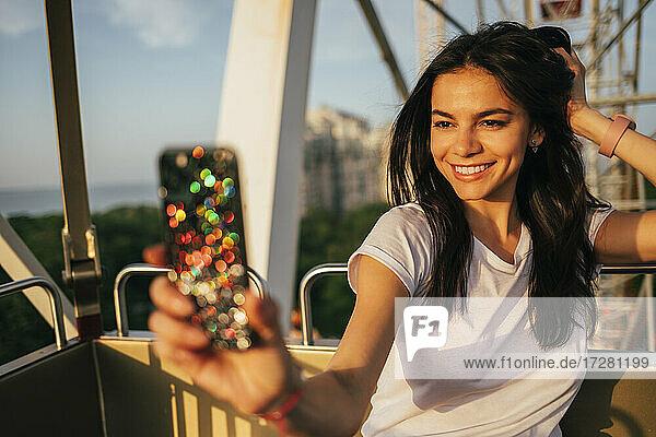 Happy beautiful woman taking selfie on Ferris wheel at amusement park