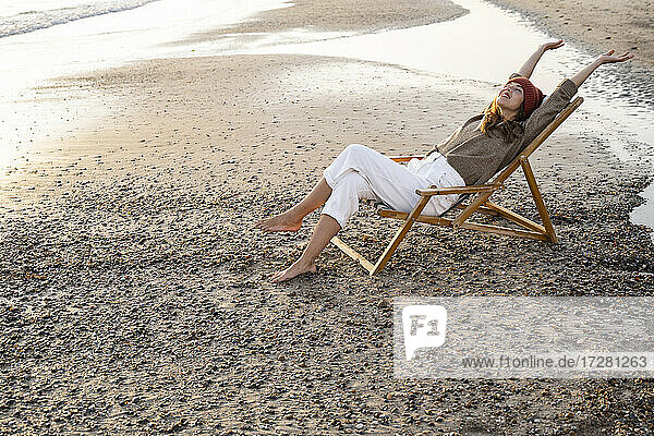 Smiling young woman sitting with legs cross and arms raised on folding chair at beach during sunset