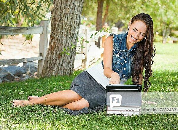 Glückliche gemischtrassige junge Studentin mit Büchern mit Computer-Tablet draußen sitzen im Gras