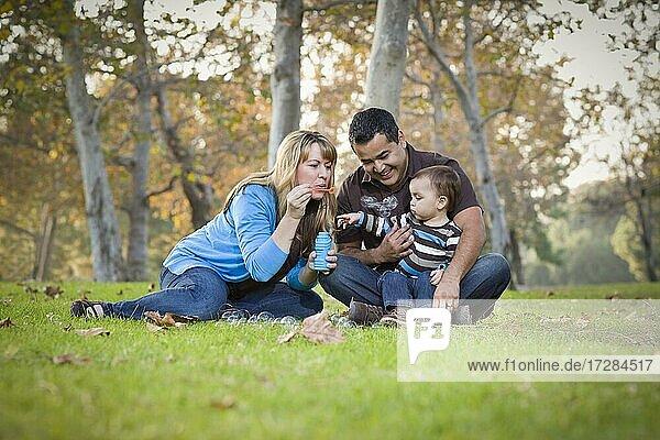 Glückliche junge gemischtrassige ethnische Familie spielt zusammen mit Seifenblasen im Park