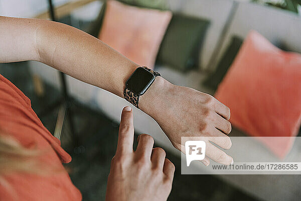 Teenage girl checking time on smart watch at home