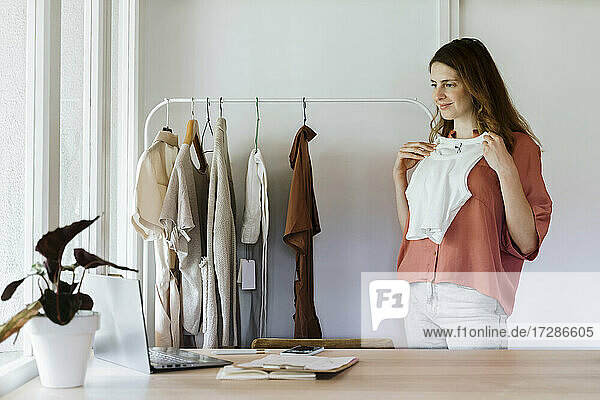 Businesswoman showing crop top during video call through laptop at home
