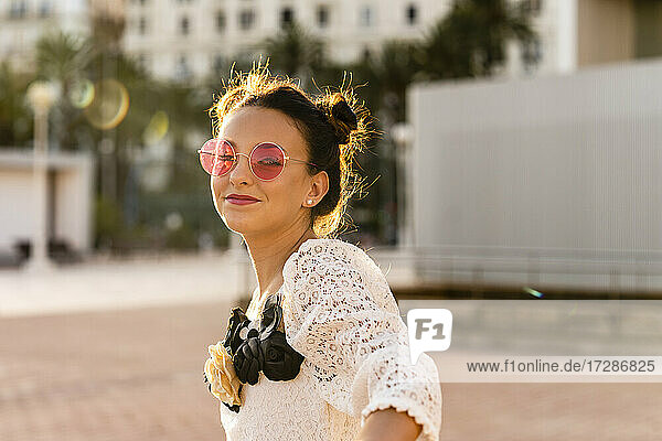 Girl wearing red sunglasses in city