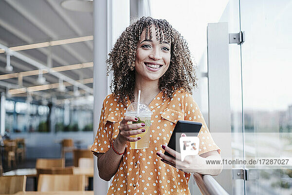 Smiling young woman with mobile phone looking away while having iced tea in balcony at cafe