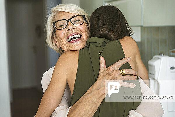 Cheerful senior woman wearing eyeglasses hugging granddaughter in kitchen