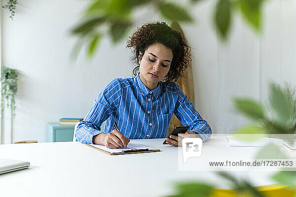 Businesswoman with mobile phone working in creative workplace