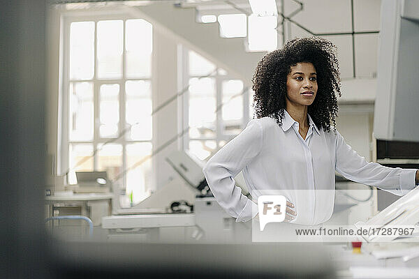 Female entrepreneur with hand on hip working with printing machinery in industry