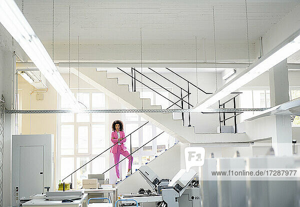Afro businesswoman with arms crossed standing on steps in industry