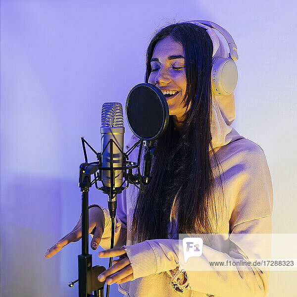 Female singer with eyes closed gesturing while singing through microphone in studio