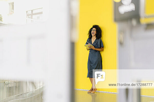 Businesswoman with digital tablet screaming in front of wall at office