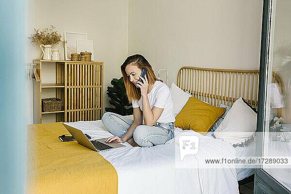 Lächelnde Frau  die zu Hause auf dem Bett sitzt und mit ihrem Handy spricht