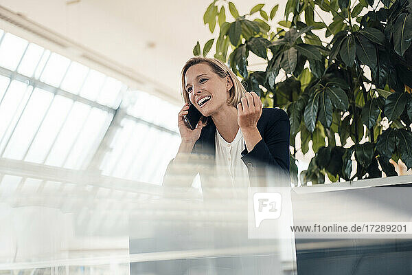 Smiling businesswoman talking on mobile phone at office