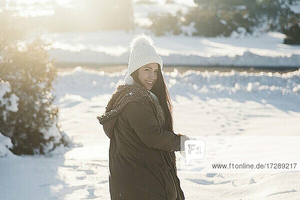 Smiling woman looking over shoulder while standing on snow during sunny day