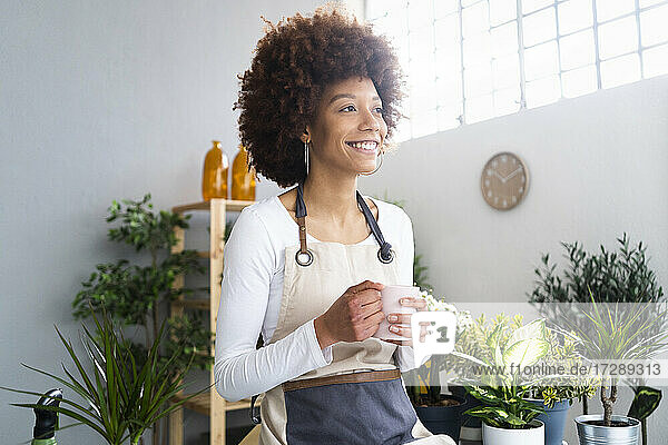 Female shop owner with coffee cup smiling while looking away at plant shop