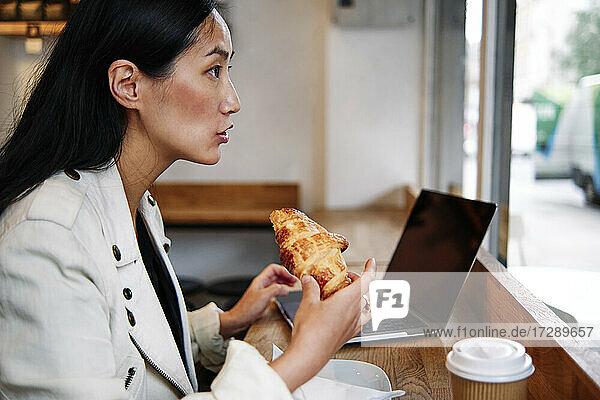Frau schaut weg  während sie ein Croissant in einem Café isst