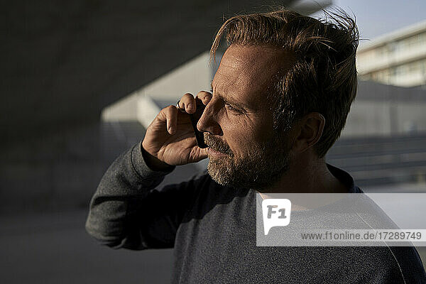 Male professional talking on mobile phone during sunny day looking away