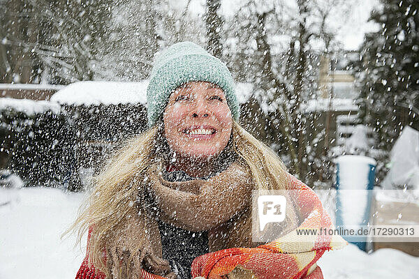 Cheerful mature woman wearing knit hat and scarf while snowing in winter