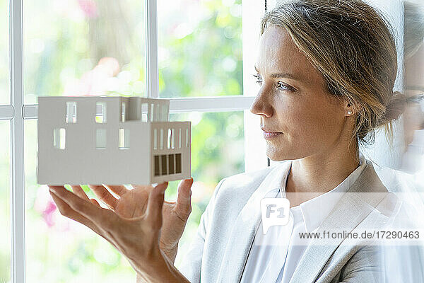 Thoughtful businesswoman with architectural model looking through window