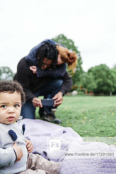 Cute son looking away while father and mother photographing in background