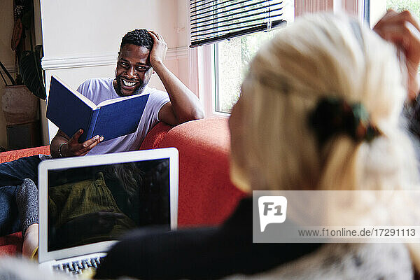 Smiling boyfriend with book looking at girlfriend in living room