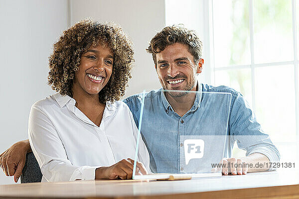 Smiling male and female entrepreneurs sitting by glass screen at office