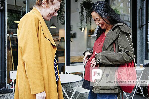 Lächelnde schwangere Frau zeigt einer Freundin im Café ihren Unterleib