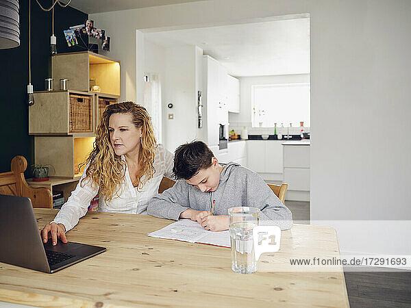 Blonde Frau benutzt Laptop bei ihrem Sohn  der zu Hause lernt
