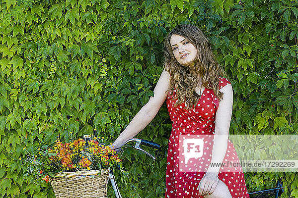 Beautiful young woman with brown hair sitting on bicycle in front of green ivy wall