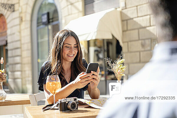Smiling woman using mobile phone while sitting at sidewalk cafe