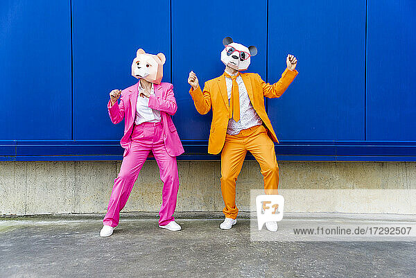 Man and woman wearing vibrant suits and bear masks dancing side by side against blue wall