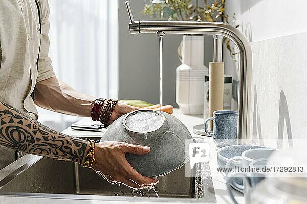 Man washing bowl in sink at home