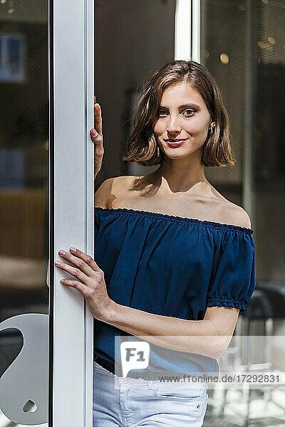 Smiling female entrepreneur with medium length hair standing at doorway