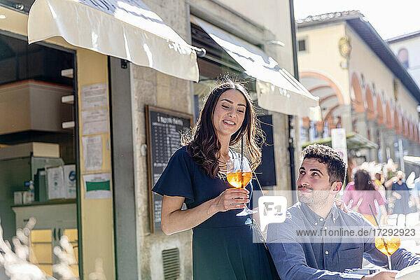 Junge Frau mit Getränk an der Seite eines Mannes in einem Straßencafé