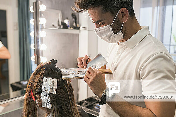 Male professional covering customer hair with foil at salon during COVID-19