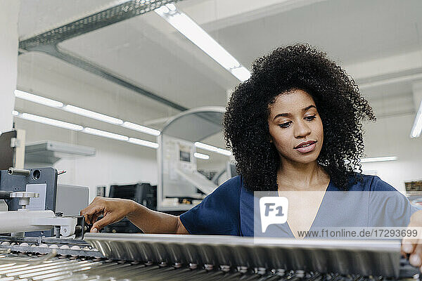 Afro businesswoman adjusting machinery at printing industry