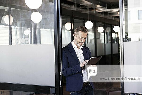 Geschäftsmann arbeitet an einem digitalen Tablet an einer Glastür im Büro