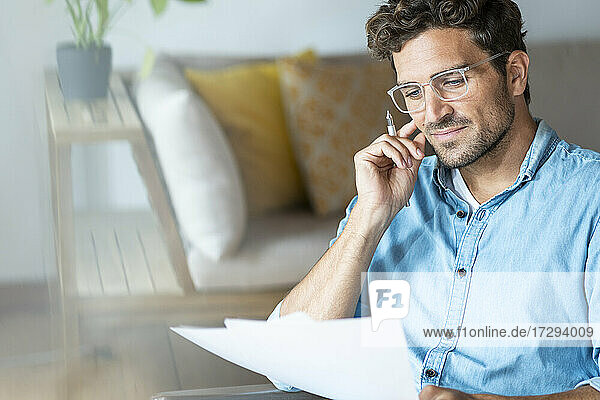 Businessman with eyeglasses reading document in office