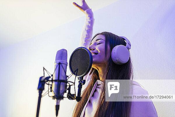 Female singer with hand raised singing at studio